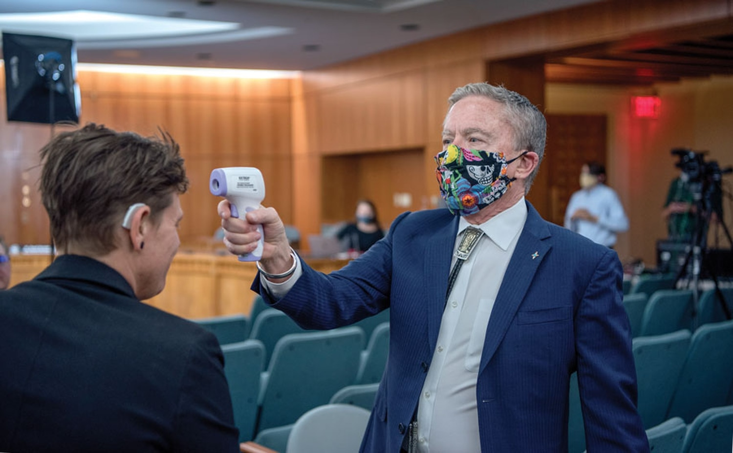 Health and Human Services Secretary David Scrase takes deaf interpreter Nixo Lanning's temperature before a public address in which Scrase interpreted the state's modeling data.