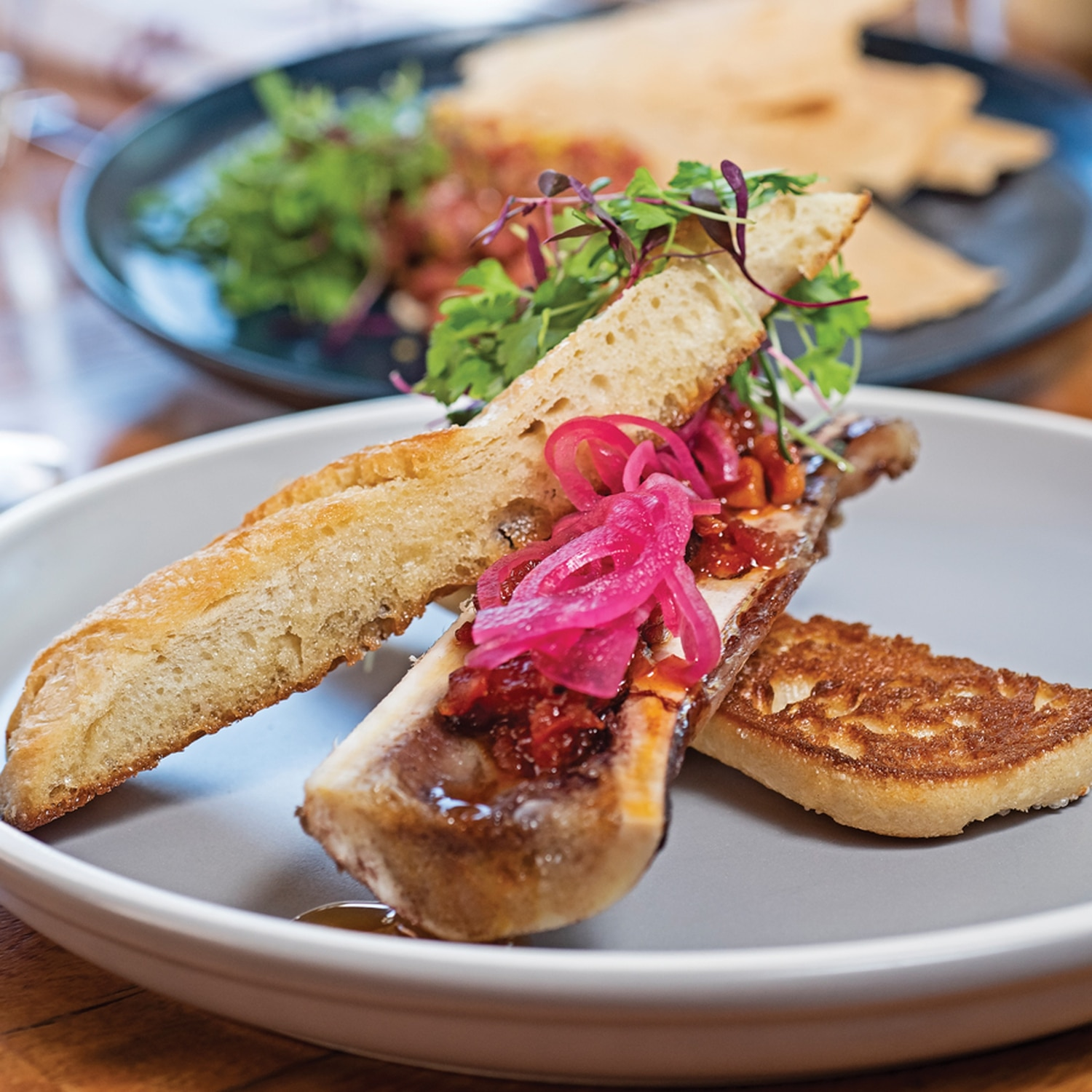 Roasted beef bone marrow with pickled red onion and tomato bacon bourbon jam.