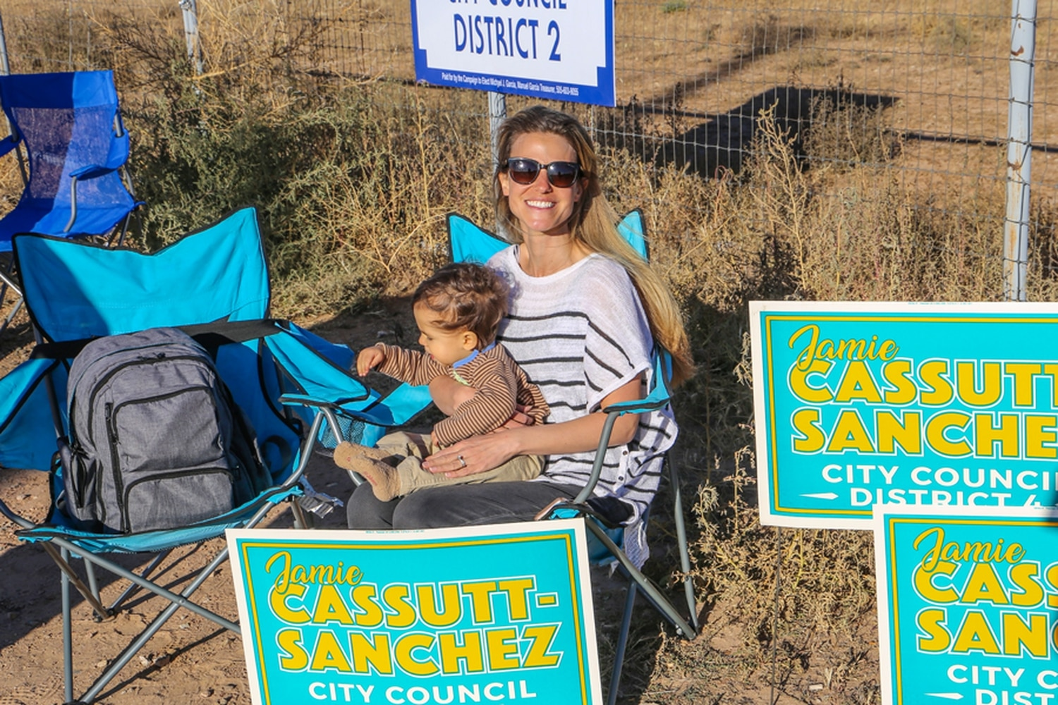 Jamie Cassutt-Sanchez and her son, Oliver, sit outside the Santa Fe County Fairgrounds on Tuesday afternoon to woo voters.