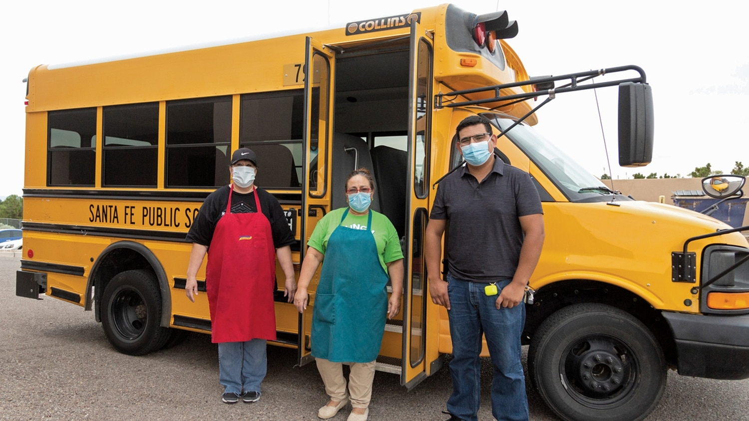 Mariam Bartleson, left, and her coworkers loaded up prepared meals onto a school bus at Chaparral Elementary School in Santa Fe on June 26. The team then drove to the village of Glorieta to deliver the meals to families who need them.