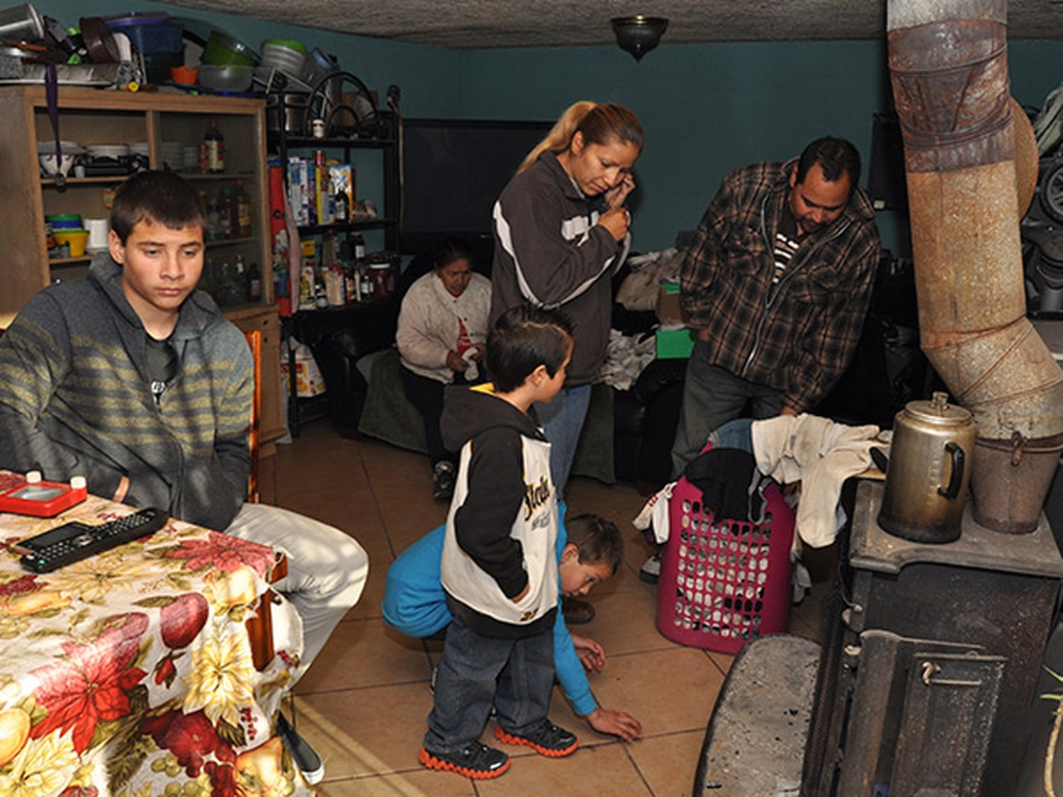 Victor and Claudia Padilla; son Kevin (14), is at left; Dylan (8) is in black and white hoodie, Brian (13) is kneeling down. The wood burning stove is the only heat source in the living room.