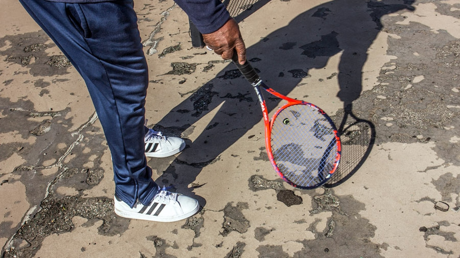 King uses a racket to point to damage in the tennis court at Herb Martinez Park.