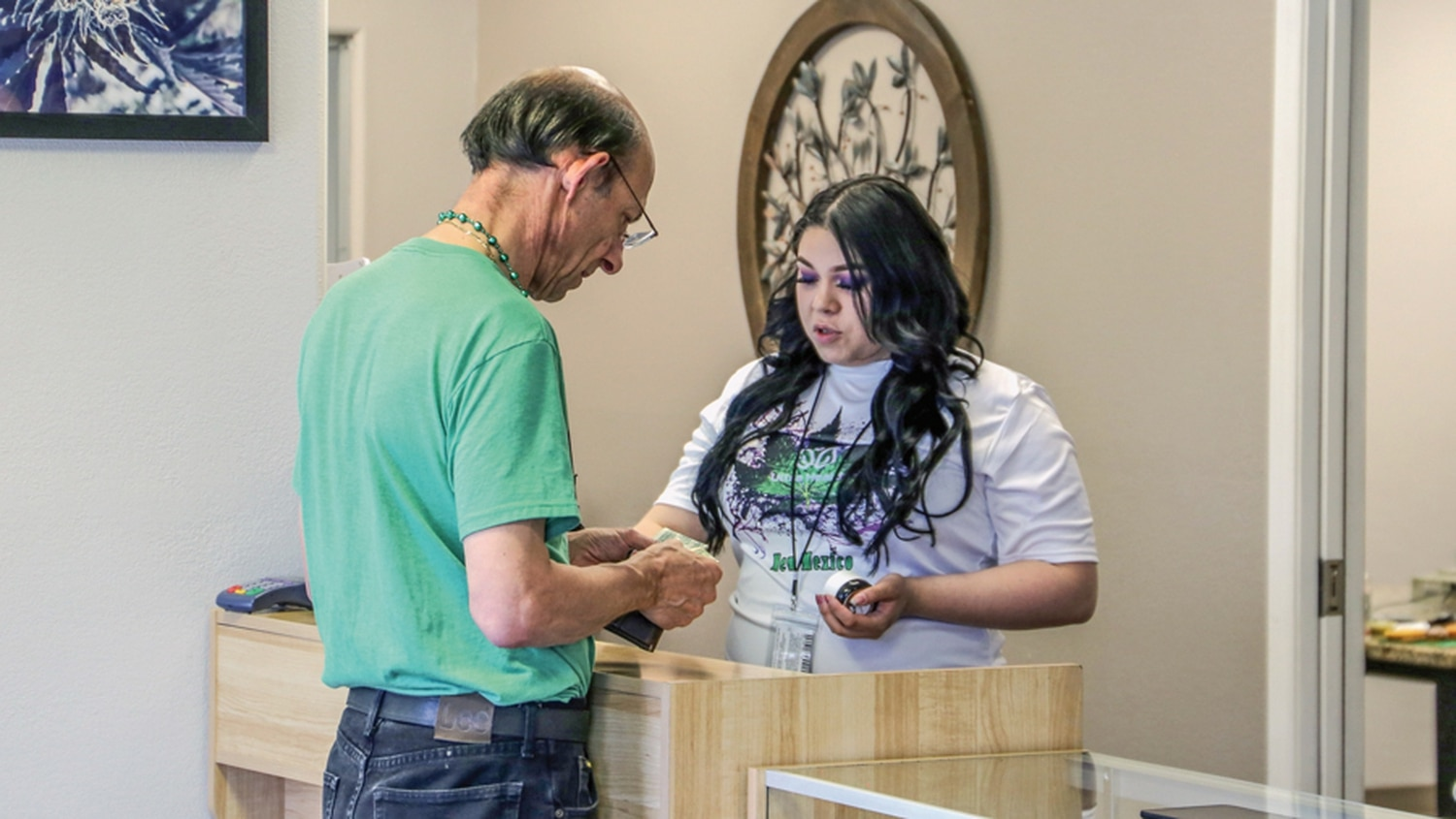 Patient John Reid consults with a budtender at Ultra Health on 4/20. Reid says product shortage has not affected him the way it has some other patients.