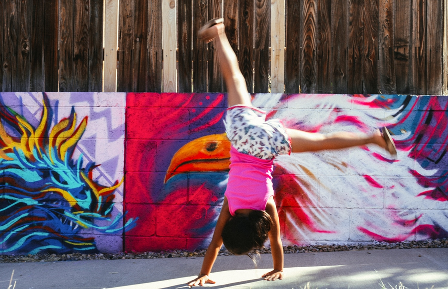 The daughter of Christina Castro of the Three Sisters Collective goes between cartwheeling and helping her mom with their portion of the mural.