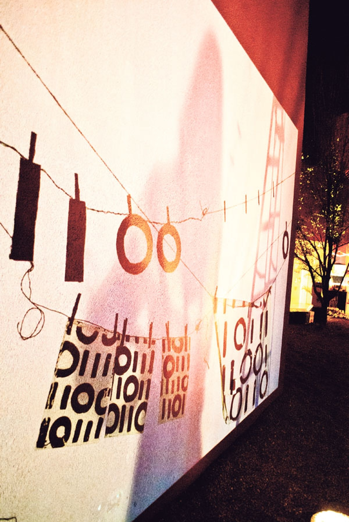 """Sandra Halpin's """"Hanging My Binary Out to Dry"""" is an interactive exhibit that combines real-world objects (the clothesline and the one-and-zero forms) with digital projections."""