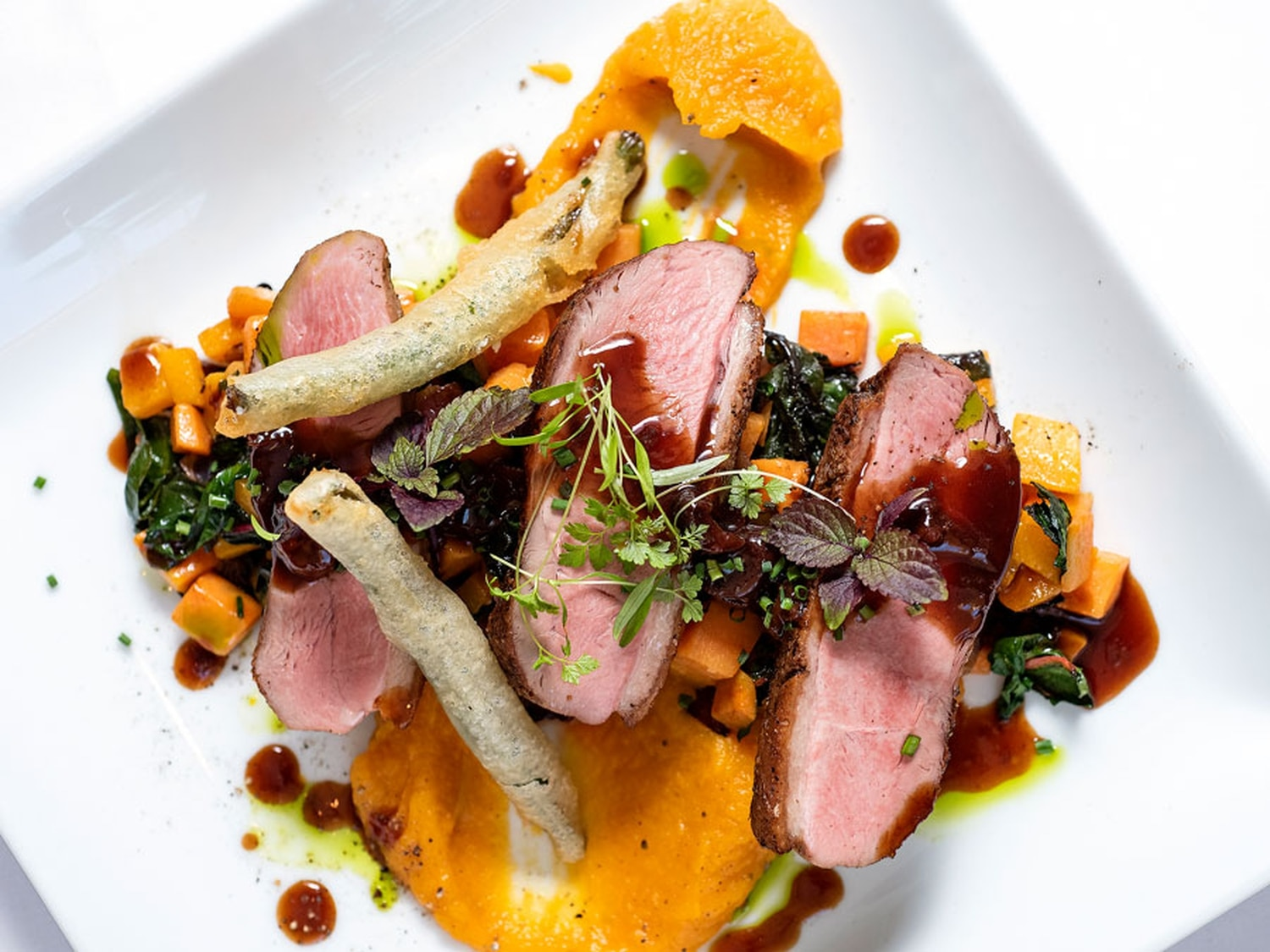 Pan roasted breast of duck with sweet potato hash, Swiss chard, sweet potato puree