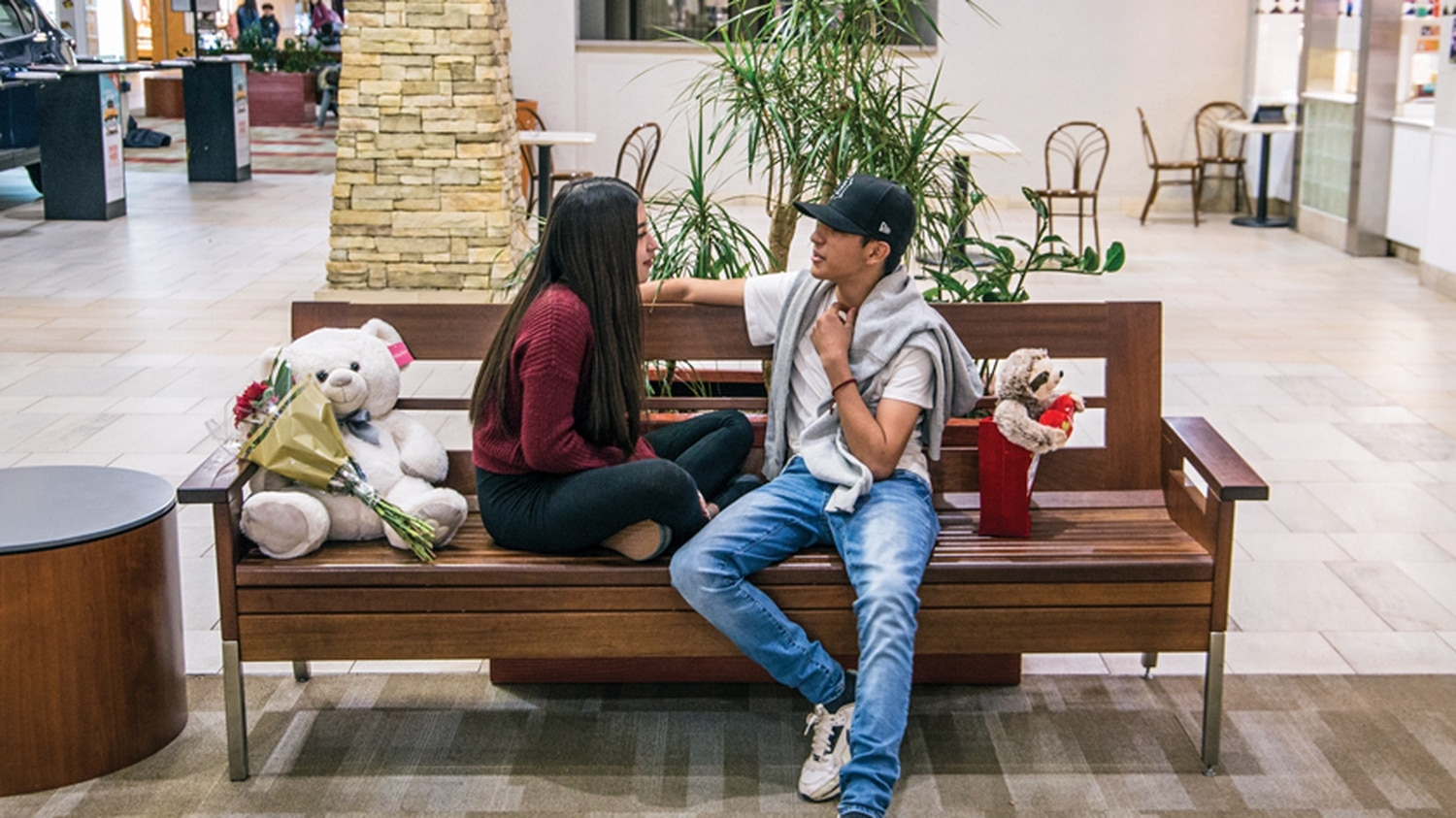 Mall seating offers a quiet, almost private date for two teens.