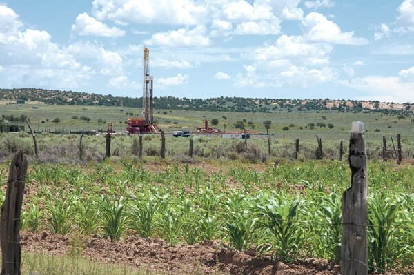 Crops share the landscape with corporate-controlled wells that are producing about 2 million barrels of oil per month in San Juan County.