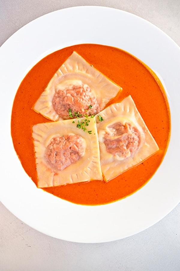 Carne adovada ravioli with Chimayó red chile-marinated pork, served with a garlic red chile cream sauce