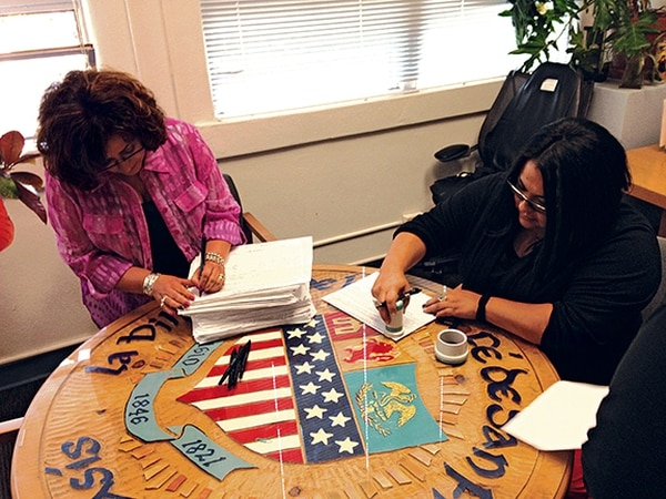 City Clerk Yolanda Vigil, at left, and recording clerk Geralyn Cardenas review petitions for the law change.