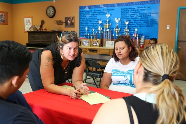 Allegra Love (left) tells a mother that her son doesn't qualify for a deferred-action work permit because of an arbitrary date. UNM Dream Team volunteer Miriam Garcia listens.