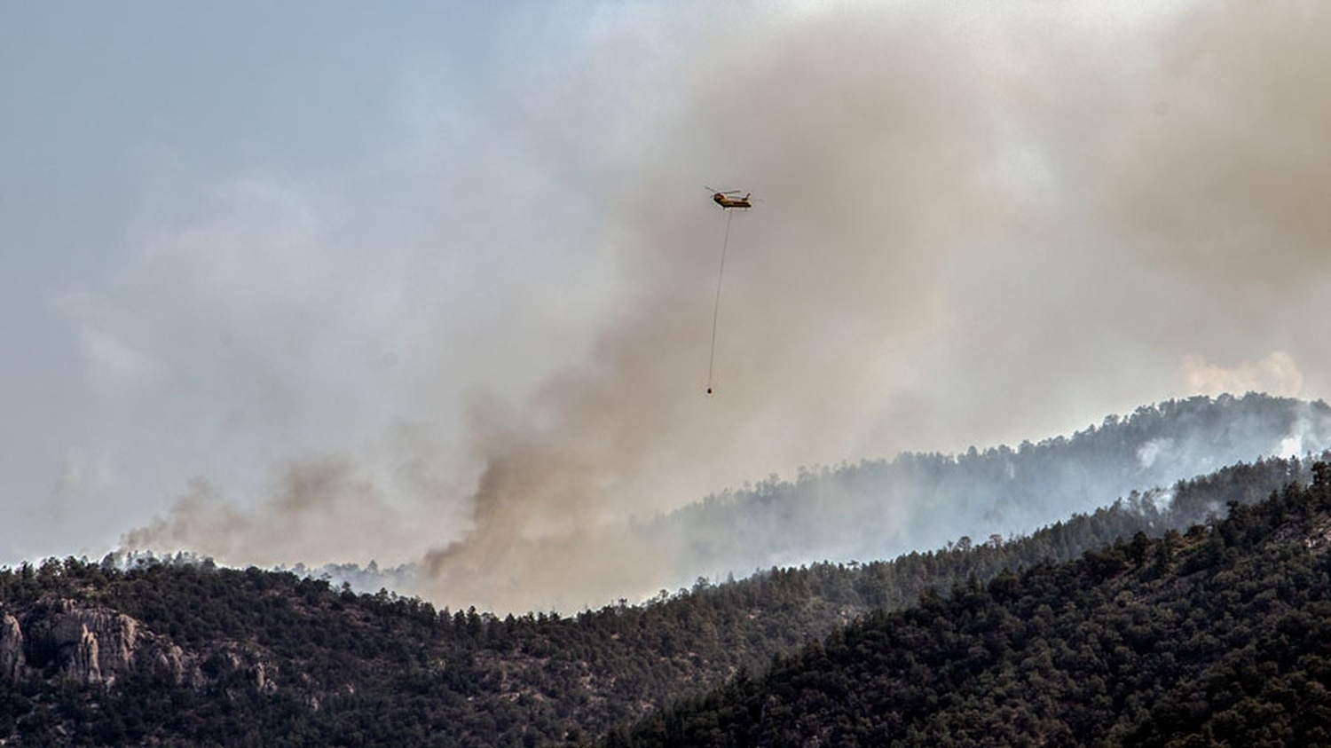 A helicopter brings water to help crews stay in control as they intentionally ignite the forest along the west edge of the Medio Fire.