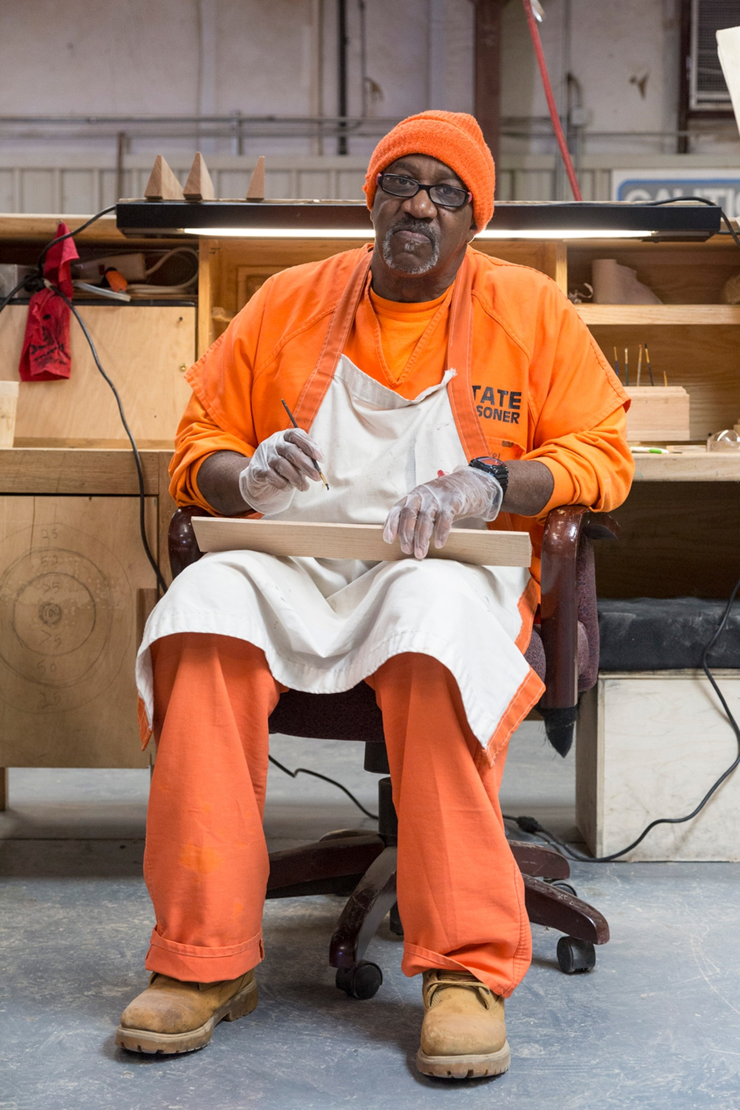 Nathan Jones, an inmate at the Central New Mexico Correctional Facility, paints a golden oak name plate.