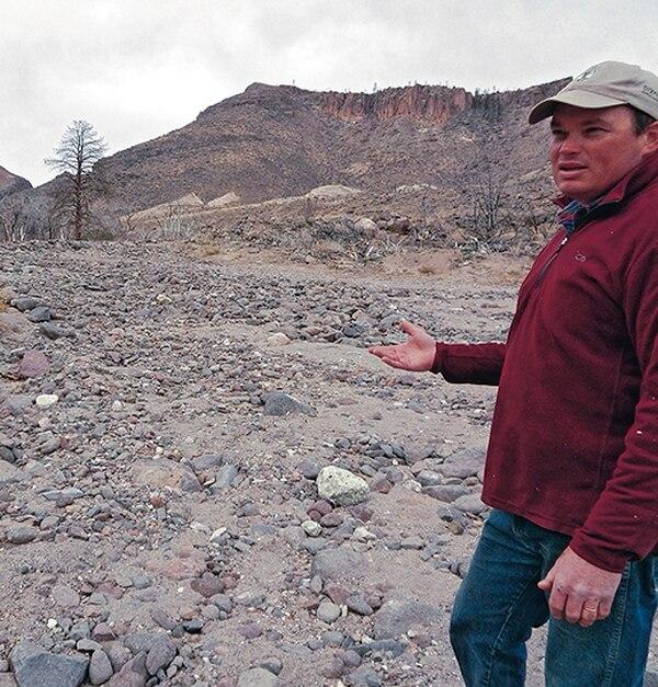 Jim Mullane points to lingering flood damage.
