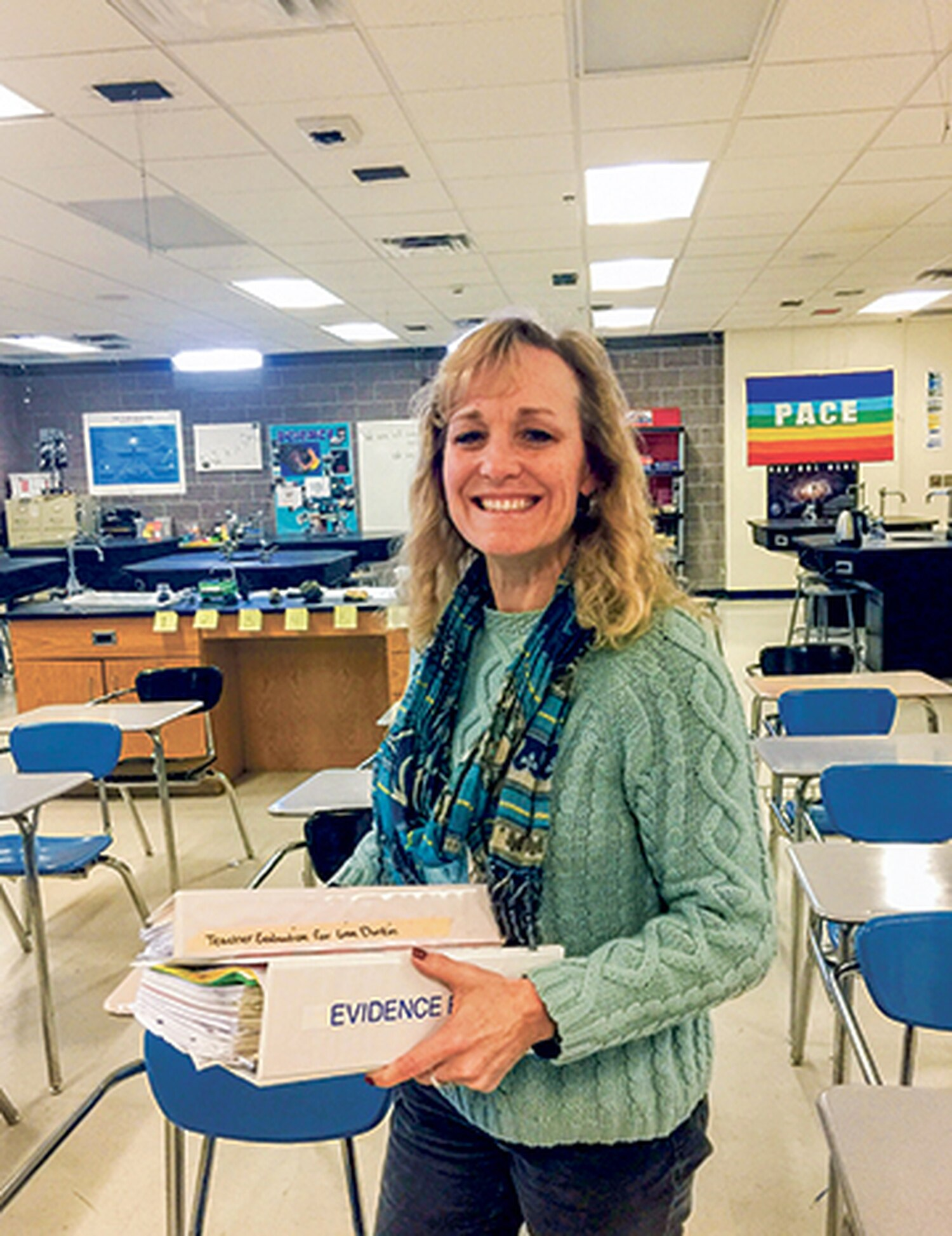 Lisa Durkin shows off the documents she compiled for her recent teacher evaluation—710 pages of them.