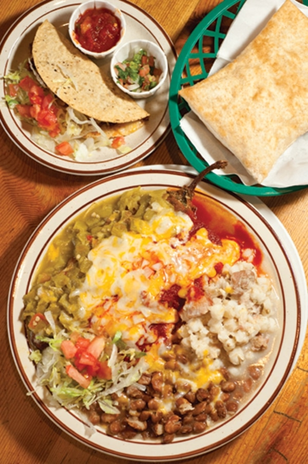 "Atris Combo with relleno, enchilada, taco, posole and beans. 193 Paseo de Peralta, 983-7401 Lunch and dinner daily; breakfast Saturday and Sunday Atrisco Café The cute little lamb on the restaurant logo isn't just for looks. The famed Talus Wind Ranch in Galisteo is the source for their roasted leg of lamb burrito with red chile ($12.50) and everything else that baas from the menu's daily specials. Find all the traditional New Mexican dishes that you desire, and expect them to be executed with care. Slurp up a bowl of menudo ($7.95), which restaurateur George Gundrey claims is a ""scientifically proven hangover cure""; spoon out a lovely cup of pureed black bean soup ($2.95) that has a slight kick along with the strong flavors of cilantro; or inhale the green chile stew, a version with huge pieces of potato and chunks of tender beef topped with a ladle-full of spicy chopped chile ($8.95/bowl, $5.25/cup). Wash it down with one of the signature cocktails patented by bartender Mary Jane Chavez such as the ""Horny Juanita,"" a tequila creation that also includes raspberry Chambord, fresh berries and a squeeze of lime with a sugar rim ($9). Grab the honey and make the sopaipilla your final act, unless you saved room for flan. -JAG"