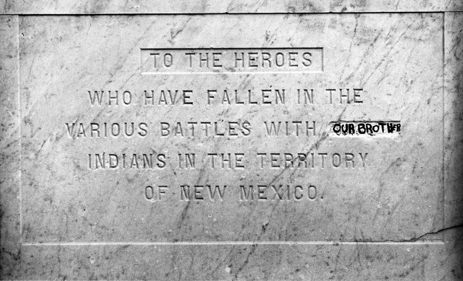 """""""Our brother"""" in black marker replaces """"savage"""" on the Plaza obelisk in Santa Fe, New Mexico, 1991."""