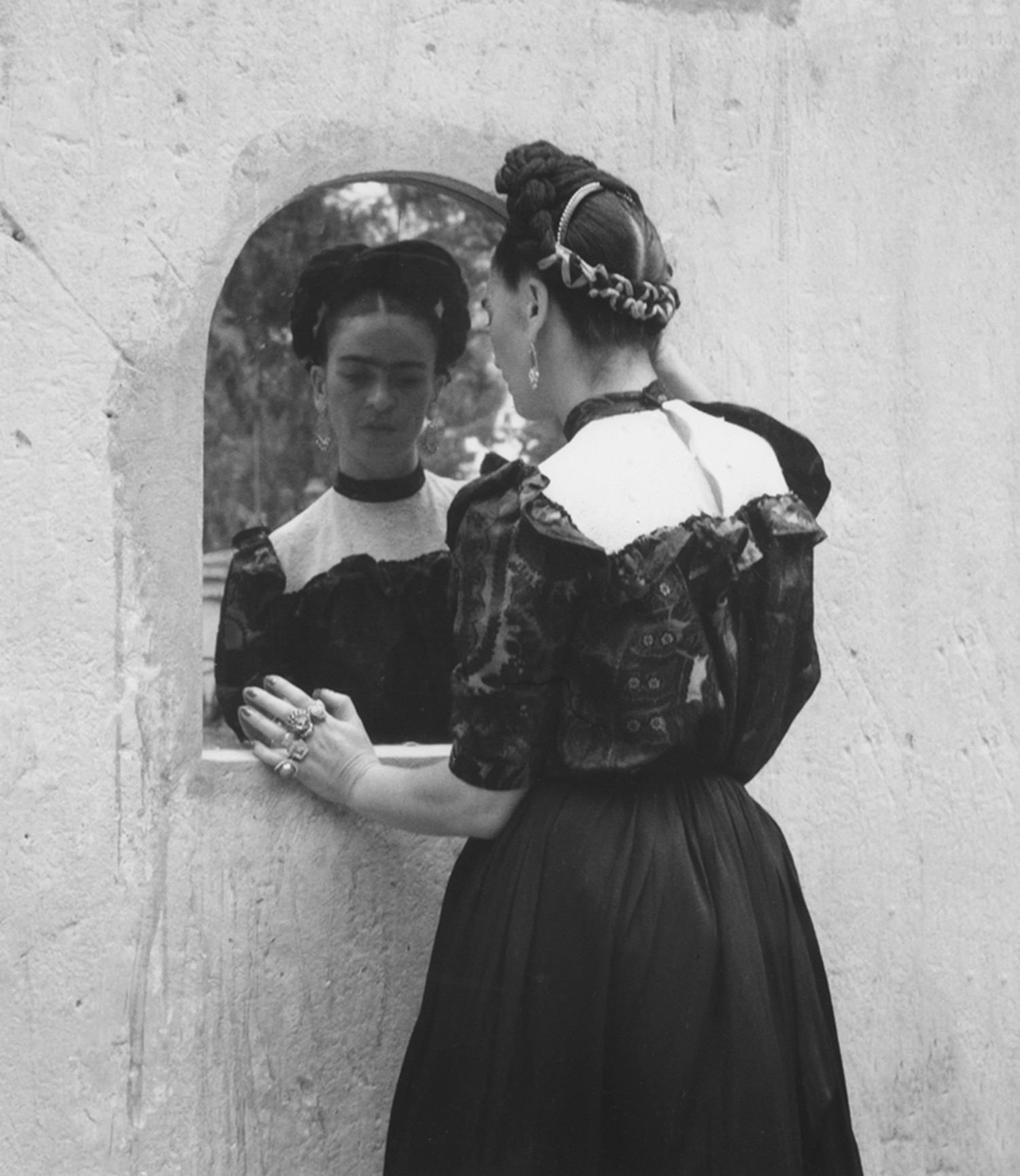 """""""Frida Looking into the Mirror"""" by Lola Alvarez Bravo shows Kahlo in the garden at her family home in Mexico City, Casa Azul."""