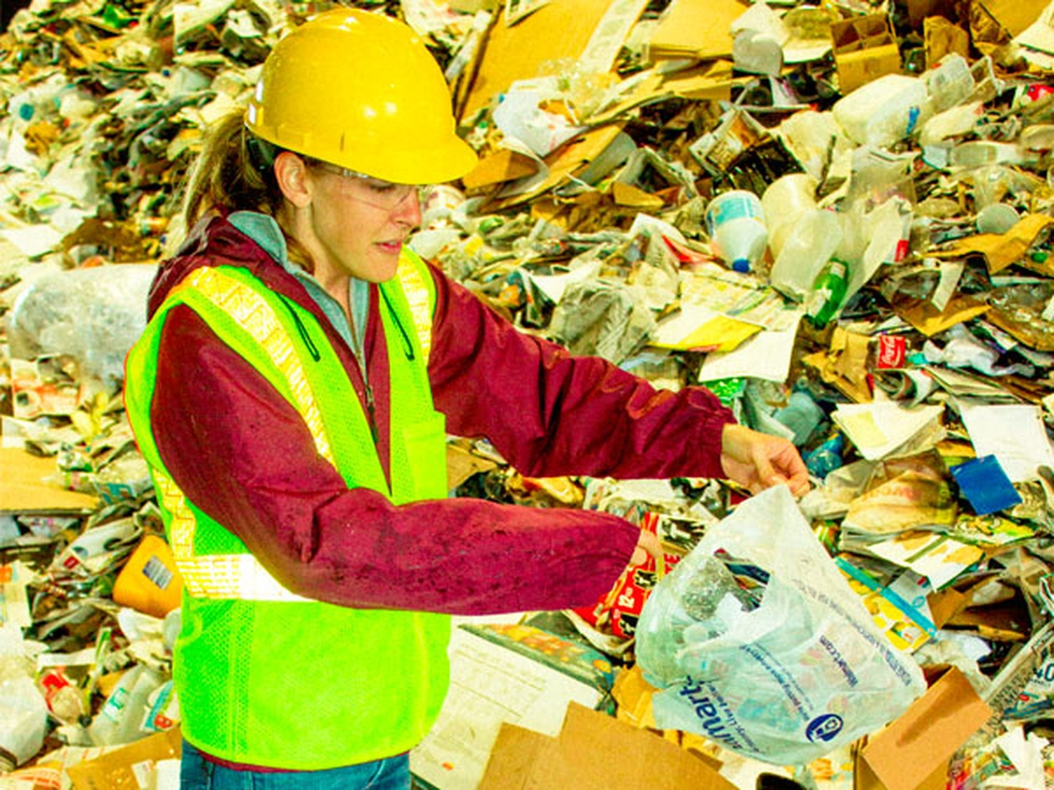 Lisa Merrill pulls a plastic bag from a pile of materials at the recycling center. The bags jam machines and stall sorting.