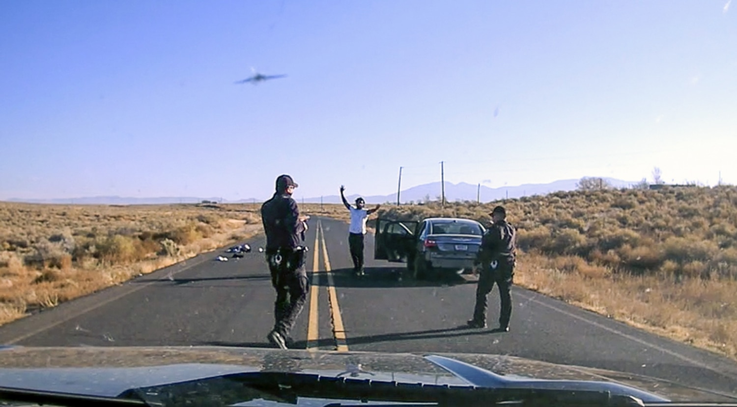 Dashcam video from New Mexico State Police shows Officer Gene Gonzales at left and Sgt. Robert Carrejo at right. Rodney Applewhite, center, had been kneeling with his hands up, but stood up when the police told him to. Carrejo then approached him with handcuffs.