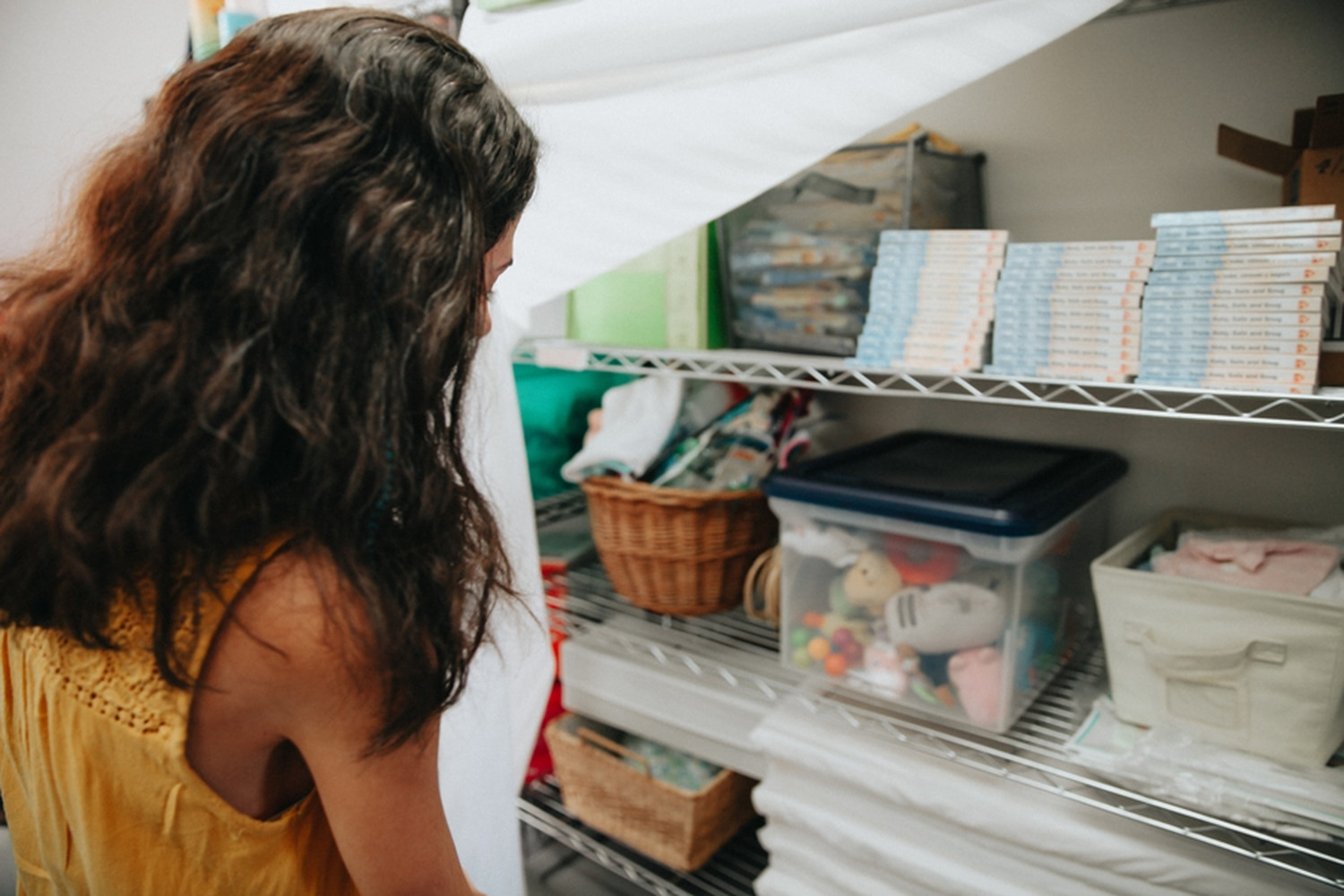 Many Mothers Executive Director Antoinette Villamil pushes back a thin white sheet acting as a curtain to cover dozens of books, toys and other baby supplies.