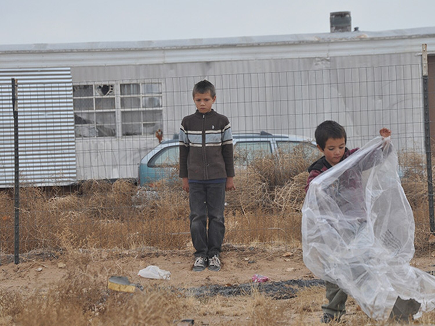 Brian (13, up against fence) and Dylan (8, with plastic bag) Padilla cleaning up their yard.