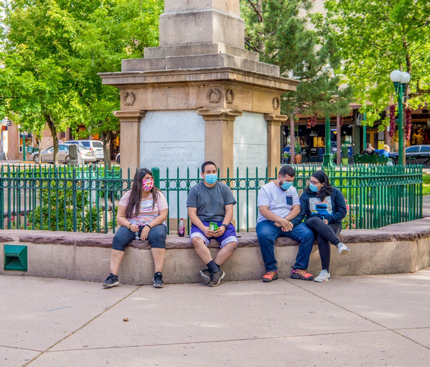 Modesto Molendrez, center right, sits along the obelisk at the center of the plaza with his wife Yuritzy, far right, his cousin Diego Becerra, center left, and Becerra's wife, Jasmine, far left.