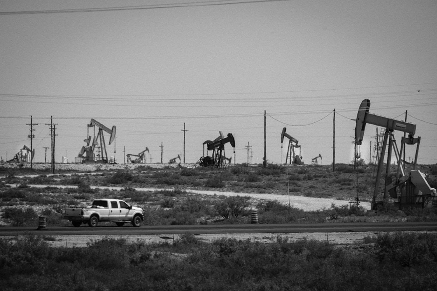 A truck drives in front of a few of the thousands of wells pulling up oil in the Loco Hills area of the Permian Basin north of Carlsbad.