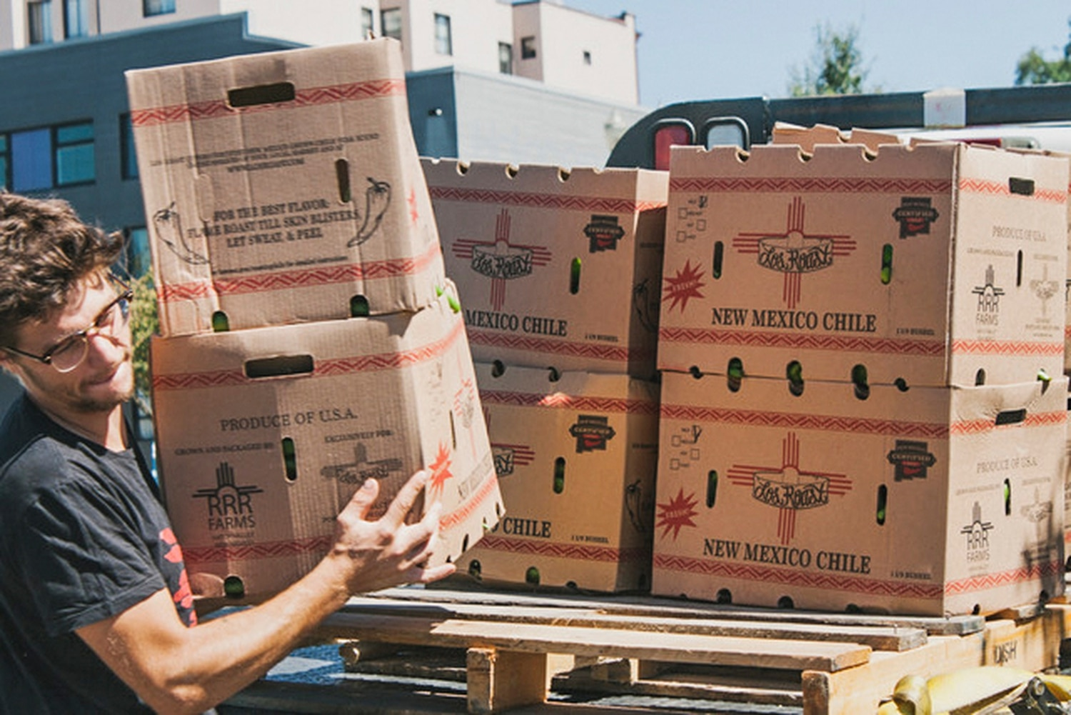 Marshall Berg carries 25-pound boxes of fresh New Mexican green chile