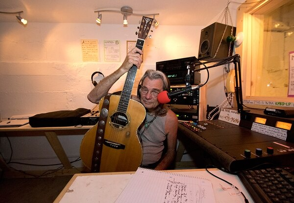 DJ Jerry Faires poses with his guitar during a song break.