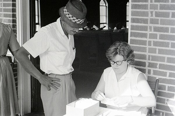 Volunteer Beth More and a local resident at a voter registration event in a church.