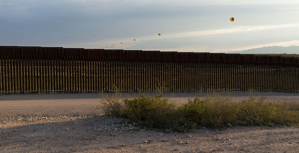 Repellent Fence soars above the US-Mexico border fence. The barrier is a patchwork of different styles. There are vertical pylons (shown here), interlinked X's, and lines of upright and inverted crosses.