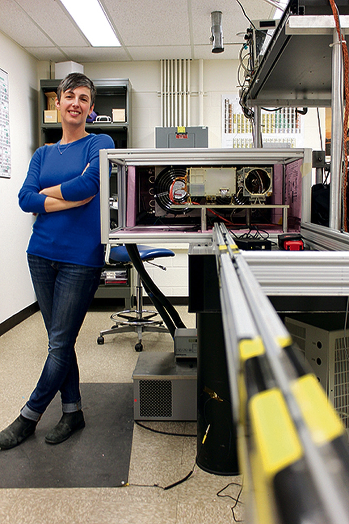 """Nina Lanza's car, like others on the team, bears a bumper sticker reading, """"My other vehicle zaps rocks on Mars."""" She poses in here the lab near the business end of the laser."""
