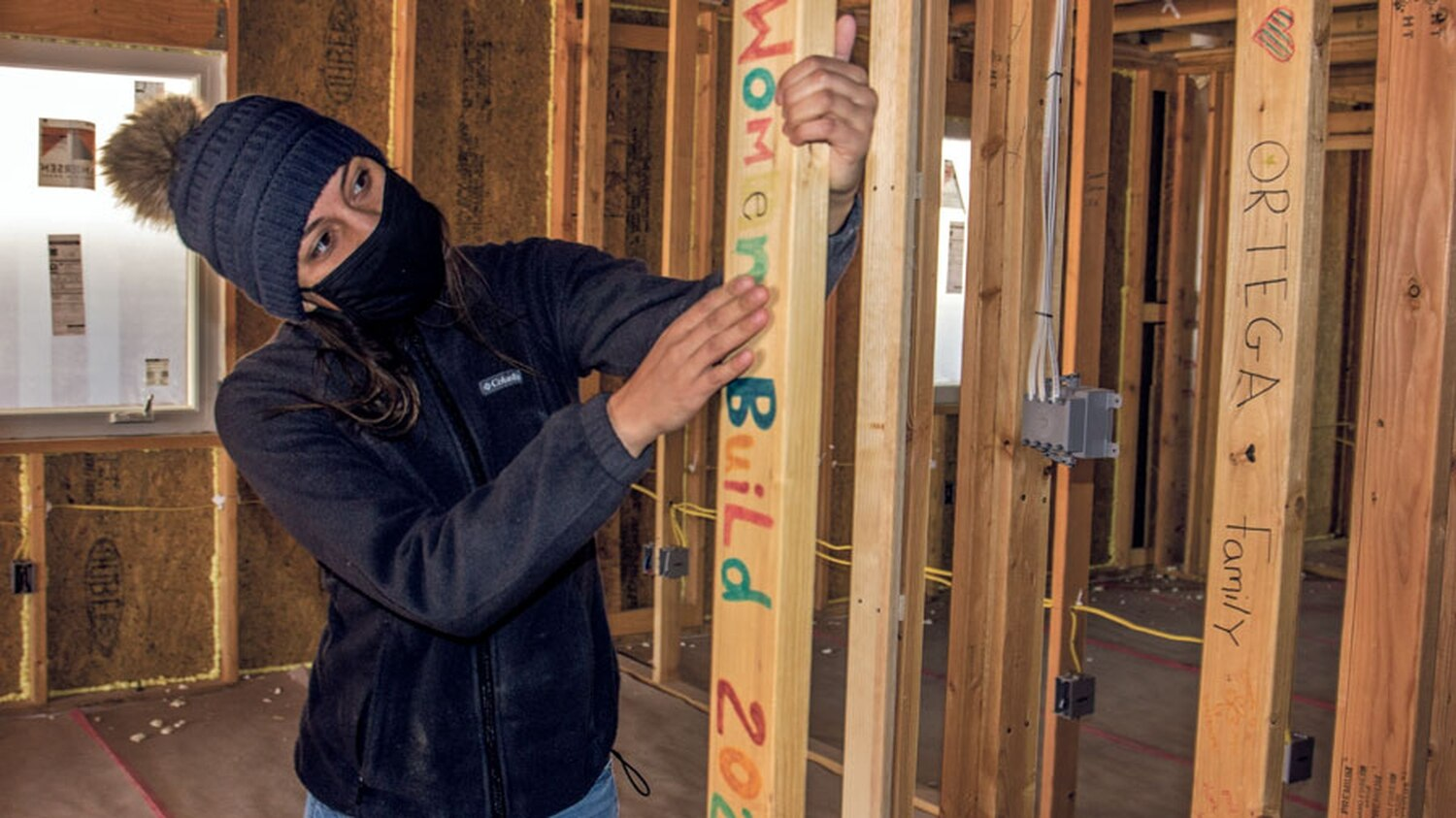 Ivette Ortega shows SFR where friends, family, and other Habitat for Humanity volunteers signed their names and wrote notes of encouragement on the frame of her house.