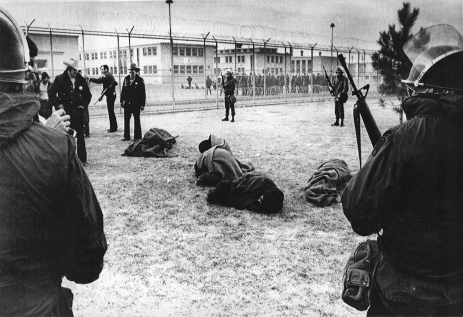 Members of the National Guard watch inmates wrapped in blankets following the riot at the Penitentiary of New Mexico oustide Santa Fe in 1980.