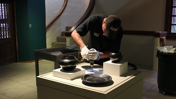 A worker installs pieces for an upcoming exhibit.