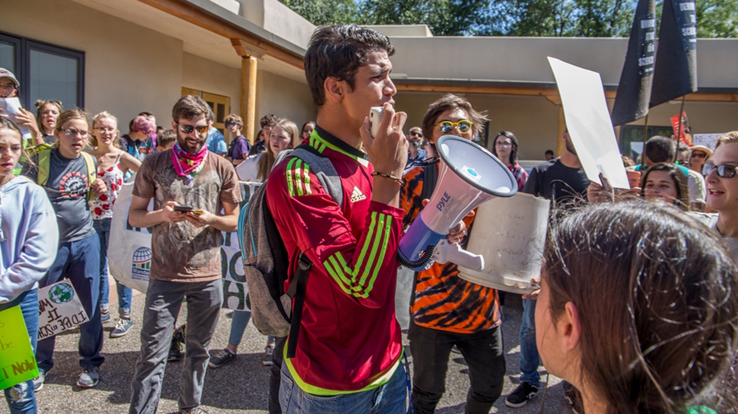 """Alejandro Ortiz, a Venezuelan student at the United World College in Las Vegas New Mexico, addresses the crowd who shouts back his words in response. """"We Strike to save ourselves, and to save the ones coming after us!"""" he calls."""