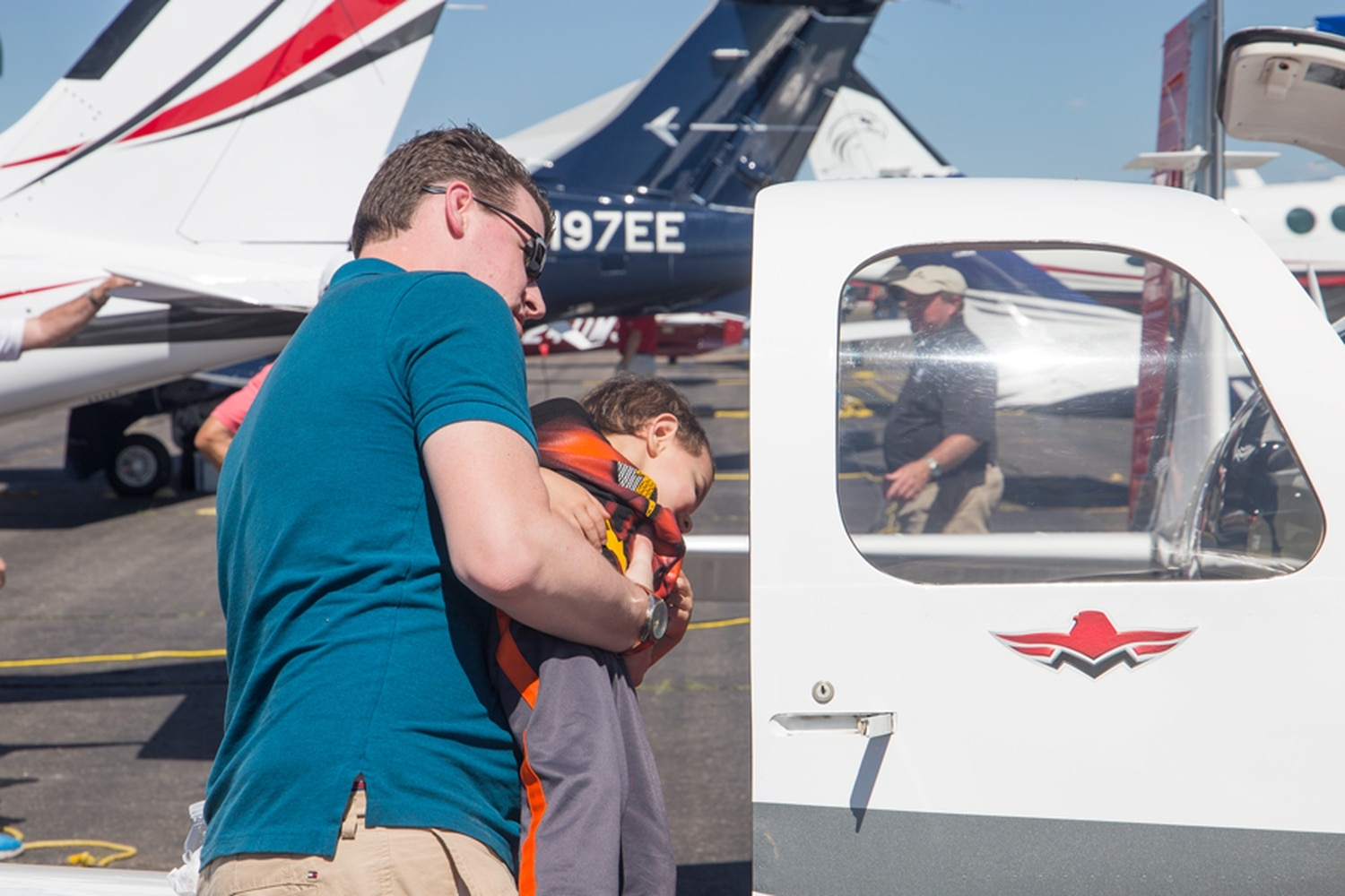 Adam Bentley hoists his son, Jonathan, to look at a Mooney Acclaim plane.