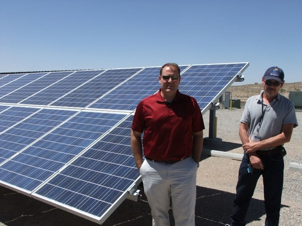 Jon Hawkins, PNM's manager of advanced energy technology and strategy (right), and Steve Willard, project manager for the Prosperity Energy Storage Project, show off one of the solar panels involved in the project.
