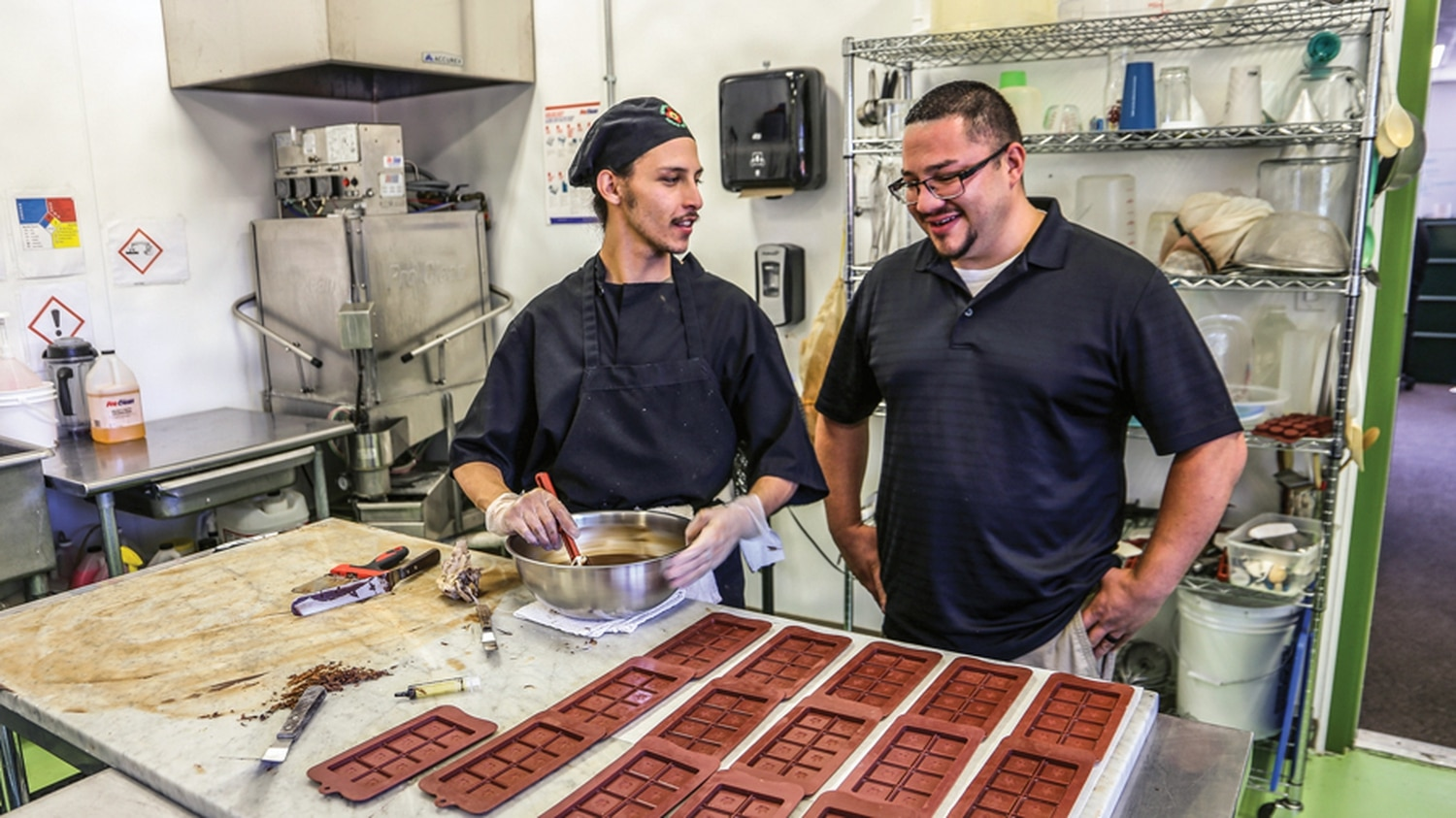 Michael Salazar, left, prepares chocolate containing cannabis in the kitchen at New MexiCann dispensary in Santa Fe as Josh Aldarete looks on.