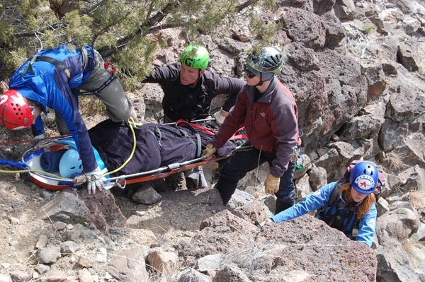 In a practice scenario, Atalaya SAR volunteers work to carry an injured evacuee up over the edge of a cliff.