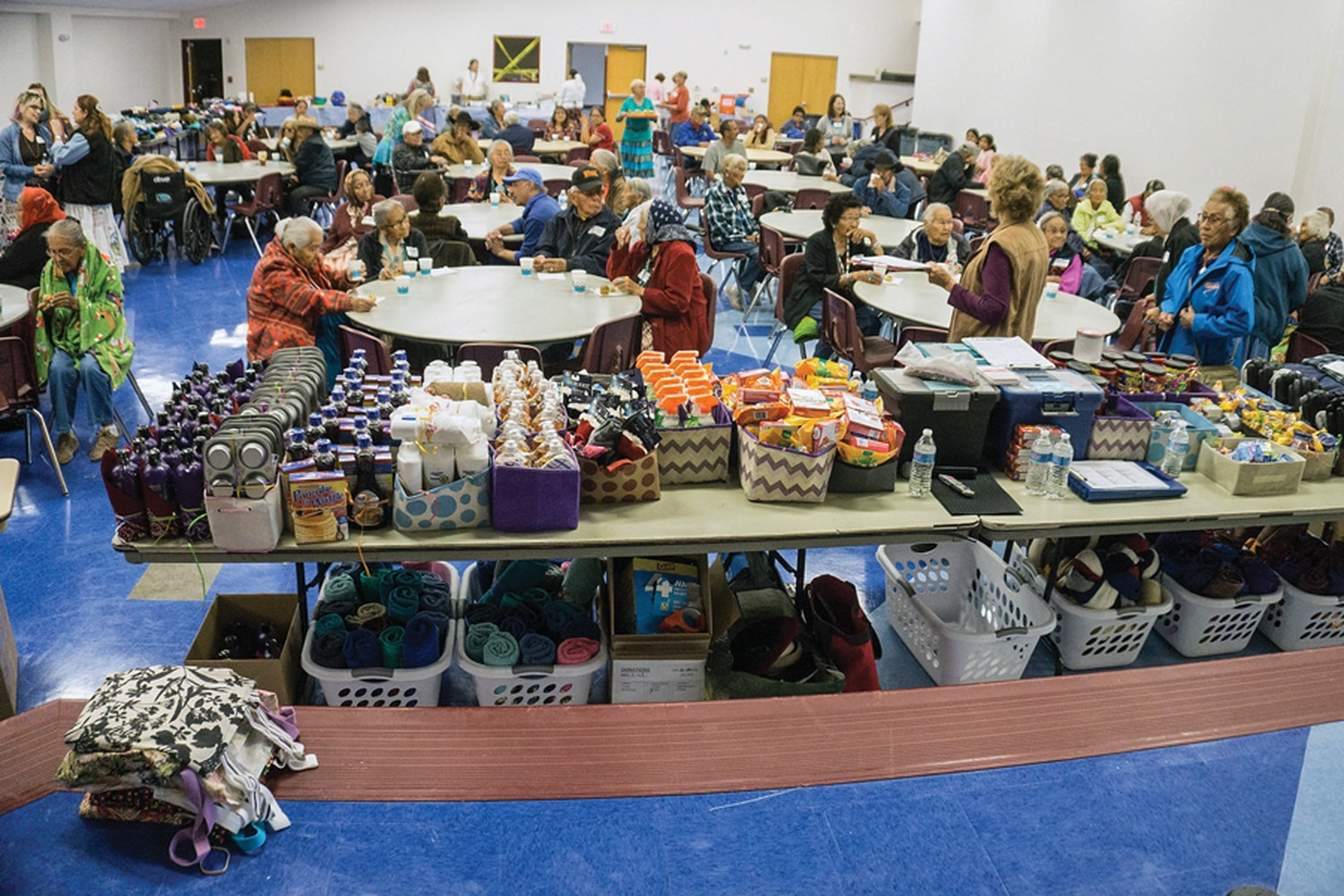 Elders gather in front of boxes full of giveaways at the food run at Diné College in Tsaile.