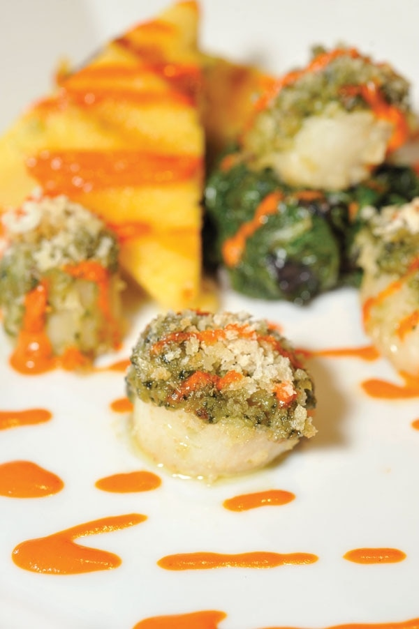 Pesto-crusted diver scallops with spicy polenta, wilted greens and red bell pepper oil