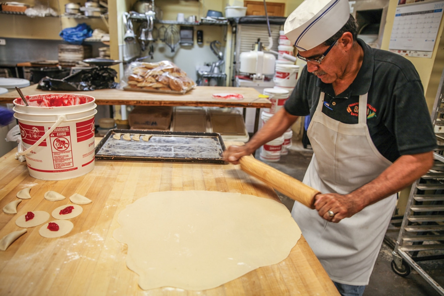 Cesar Araiza rolls out dough for fresh beer empanaditas in the kitchen of his bakery and store.