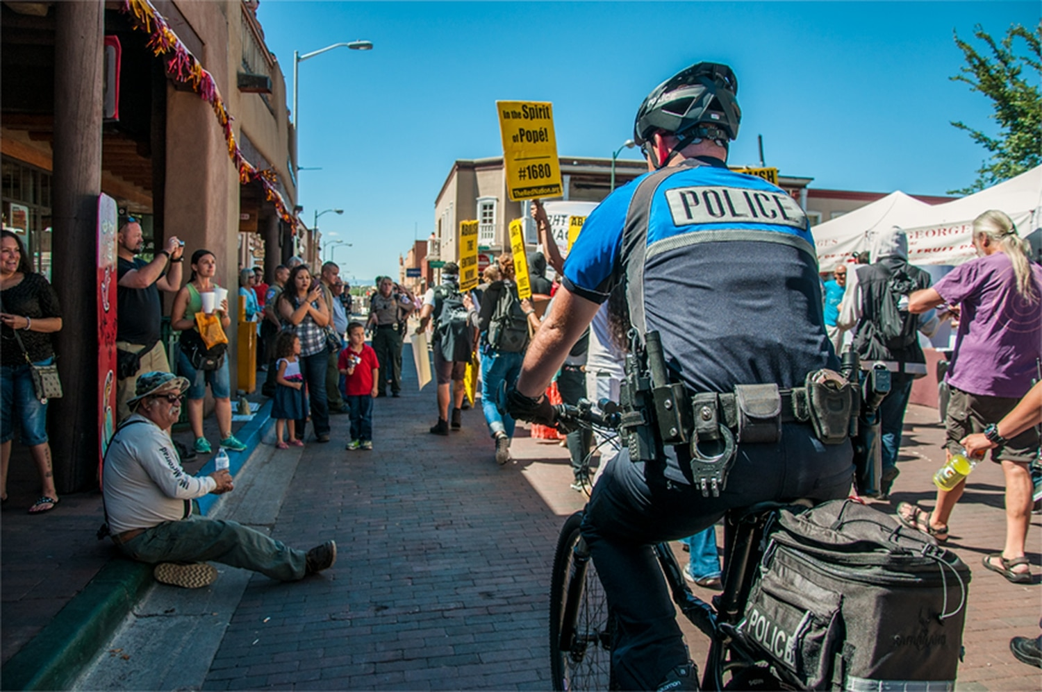 SFPD bicycle patrols cruised the streets last year on the Plaza during a protest at the Fiesta Entrada.