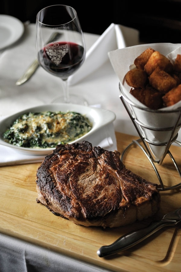 Parisian cote de boeuf for two: dry-aged prime bone-in ribeye with creamed spinach and roasted garlic tater tots