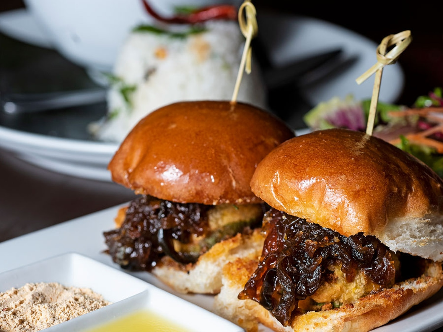 Bombay sliders with spicy potato patties, caramelized onions, mint and tamarind chutney, on a soft bun