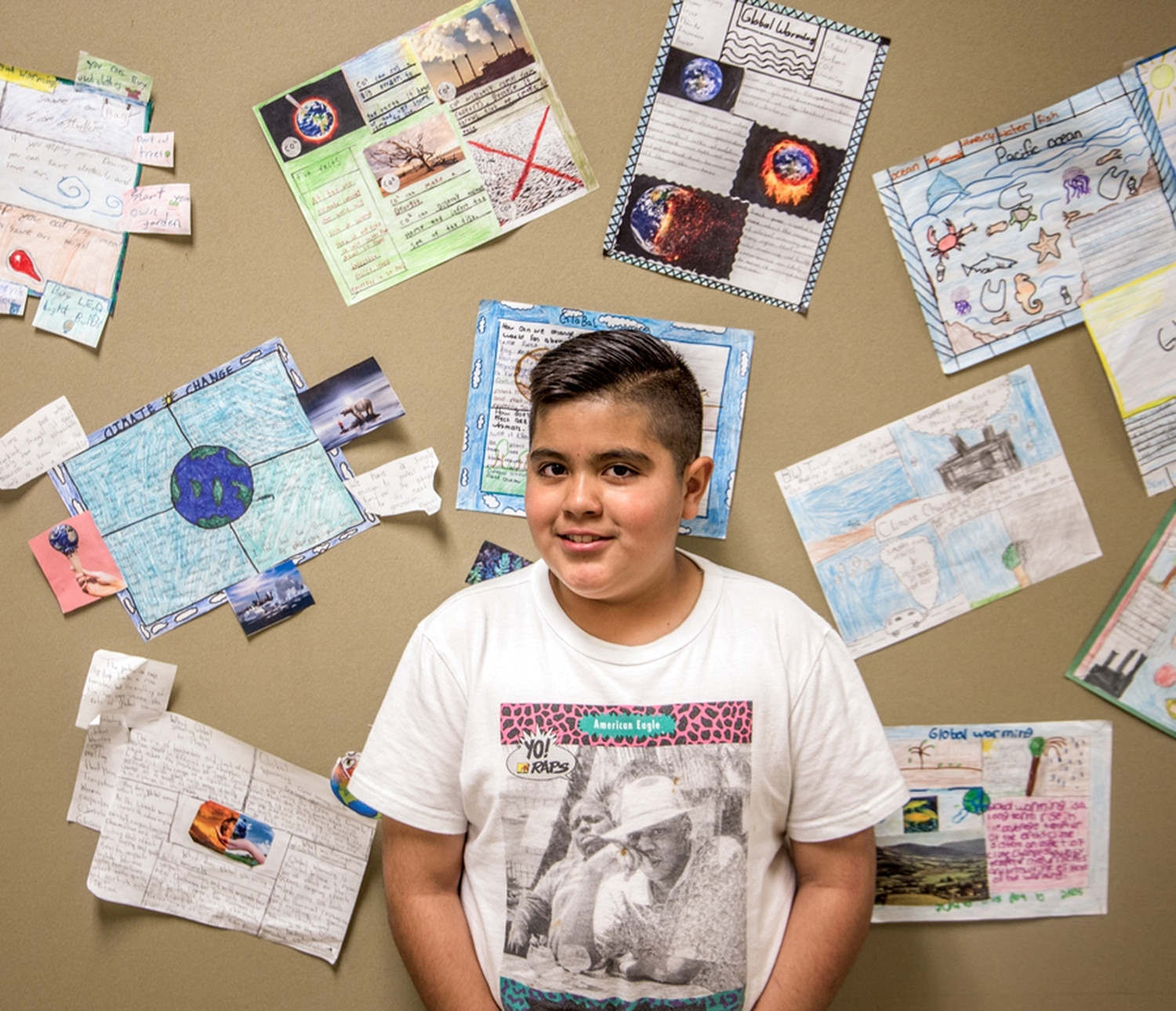 Rurabi Cerda, a fifth-grader at El Camino Real Academy, stands in front of class projects on climate change.