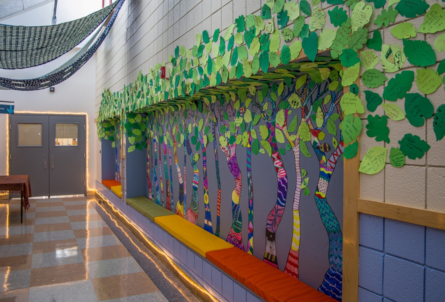 "The ""Forest of Gratitude"" mural, painted by Ortiz Middle School students, features leaves with messages written by youth participants of the Sky Center's services and their families."